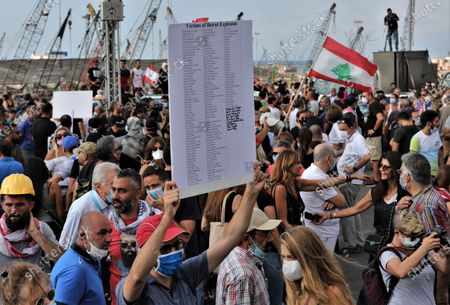 Anti-government protestors carry placards with the names of  those killed as they gather near the devastated harbor area to commemorate the victims of the explosion that took place just one week earlier, in Beirut, Lebanon, 11 August 2020. The Lebanese Health Ministry said at least 160 people were killed, and more than 6,000 injured in the Beirut blast that devastated the port area on 04 August and believed to have been caused by an estimated 2,750 tons of ammonium nitrate stored in a warehouse