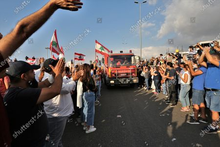 Anti-government protestors applaud as they greet firemen as they gather near the devastated harbor area to commemorate the victims of the explosion that took place just one week earlier, in Beirut, Lebanon, 11 August 2020. The Lebanese Health Ministry said at least 160 people were killed, and more than 6,000 injured in the Beirut blast that devastated the port area on 04 August and believed to have been caused by an estimated 2,750 tons of ammonium nitrate stored in a warehouse