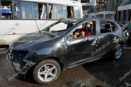 A man drive his damaged car near the devastated harbor area as anti-government protestors gather to commemorate the victims of the explosion that took place just one week earlier, in Beirut, Lebanon, 11 August 2020. The Lebanese Health Ministry said at least 160 people were killed, and more than 6,000 injured in the Beirut blast that devastated the port area on 04 August and believed to have been caused by an estimated 2,750 tons of ammonium nitrate stored in a warehouse.