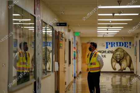 A school staff member waits in the hallway as Los Angeles Unified School District Superintendent Austin Beutner takes a tour of Burbank Middle School with Principal Christine Moore on Friday, Aug. 7, 2020 in Los Angeles, CA. As the academic school year looms, preparations have been under way to make campuses safe inside and out, even though the school year will start with distance-learning only because of the surging coronavirus pandemic. (Kent Nishimura / Los Angeles Times)