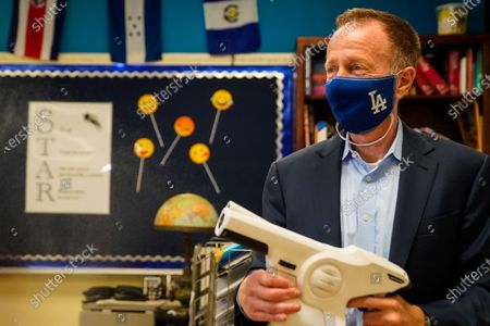 Stock Photo of Los Angeles Unified School District Superintendent Austin Beutner demonstrates the use of sanitizing tools while taking a tour of Burbank Middle School with Principal Christine Moore on Friday, Aug. 7, 2020 in Los Angeles, CA. As the academic school year looms, preparations have been under way to make campuses safe inside and out, even though the school year will start with distance-learning only because of the surging coronavirus pandemic. (Kent Nishimura / Los Angeles Times)