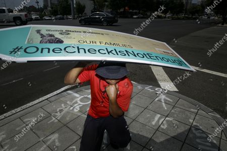 John Miller, 25, of Atlanta, spins a large check sign for the #OneCheckIsNotEnough campaign near Georgia Senator David Perdue's office, in Atlanta. The campaign said the large check is to urge politicians to support recurring direct payments in the next coronavirus relief package