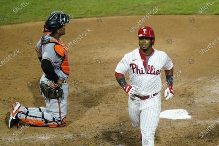 Philadelphia Phillies' Jean Segura smiles past Baltimore Orioles catcher Pedro Severino after hitting a home run off pitcher Miguel Castro during the eighth inning of a baseball game, in Philadelphia
