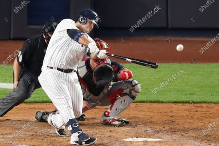 New York Yankees designated hitter Mike Ford hits a two-run double during the third inning of a baseball game against the Atlanta Braves, in New York. Braves catcher Tyler Flowers and home plate umpire Ron Kulpa, left, watch