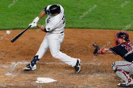 New York Yankees designated hitter Mike Ford (72) hits a run-scoring double in the eighth inning of a baseball game against the Atlanta Braves, in New York. Braves catcher Tyler Flowers (25) is behind the plate