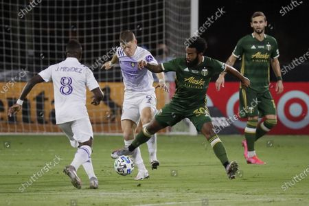 Orlando City midfielder Sebas Mendez (8) and forward Chris Mueller (9) attempt to defend Portland Timbers midfielder Eryk Williamson (30), during the first half of an MLS soccer match, in Kissimmee, Fla