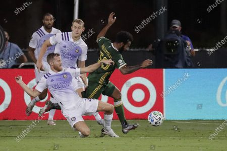 Portland Timbers midfielder Eryk Williamson (30) runs with the ball away from Orlando City midfielder Oriol Rosell (20) and forward Chris Mueller (9), during the first half of an MLS soccer match, in Kissimmee, Fla