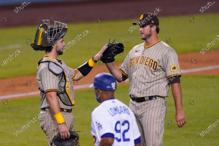 San Diego Padres catcher Austin Hedges, left, and closing pitcher Drew Pomeranz congratulate each other after the Padres defeated the Los Angeles Dodgers 6-2 in a baseball game, in Los Angeles