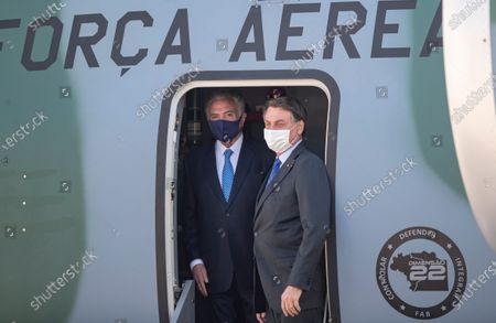 Brazilian President Jair Bolsonaro, right, and former President Michel Temer stand in the plane carrying humanitarian aid that will be sent to Lebanon, including medical supplies and experts to assist in the wake of the explosion in Beirut, at the Air Force base in Guarulhos, greater Sao Paulo area, Brazil