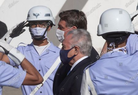 Brazilian President Jair Bolsonaro, behind center, and former President Michel Temer, front center, attend a ceremony to send off a planeload of humanitarian aid to Lebanon, including medical supplies and experts to assist in the wake of the explosion in Beirut, at the Air Force base in Guarulhos, greater Sao Paulo area, Brazil