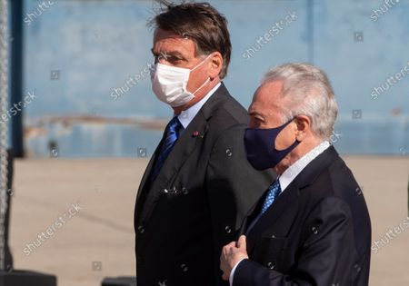 Brazilian President Jair Bolsonaro, left, and former President Michel Temer attend a ceremony to send off a planeload of humanitarian aid to Lebanon, including medical supplies and experts to assist in the wake of the explosion in Beirut, at the Air Force base in Guarulhos, greater Sao Paulo area, Brazil
