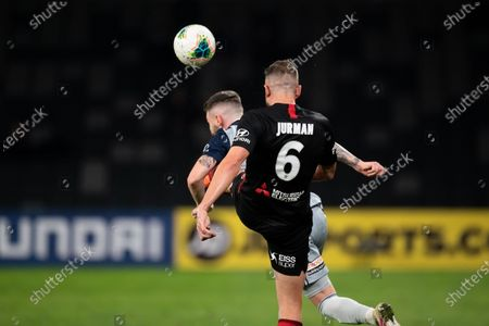Western Sydney Wanderers defender Matthew Jurman (6) accidently kicks Melbourne Victory defender Storm Roux (2) in the face