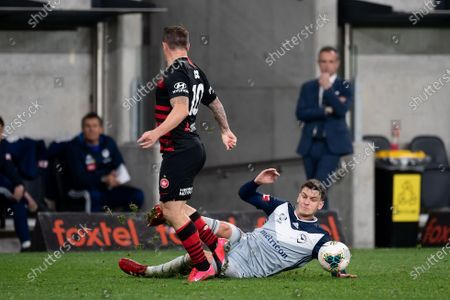 Western Sydney Wanderers midfielder Simon Cox (10) is tackled by Melbourne Victory forward Nils Ola Toivonen (11)
