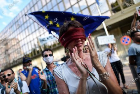 People stand in front of the German Embassy in Sofia, Bulgaria, 12 August 2020, with their eyes covered as part of an anti-government protest. The demonstration is related to the words of the leader of the European People's Party in the European Parliament Manfred Weber that EPP support current Bulgarian government of Boyko Borrisov in the fight against corruption.