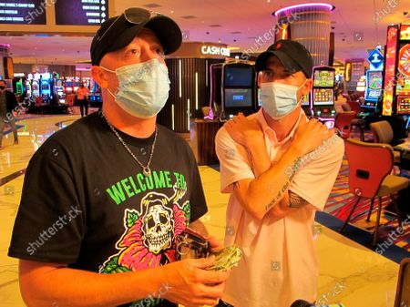 Mike McLaughlin, left, displays a wad of cash he and his friend Johnny Solis, right, planned to gamble at the Hard Rock casino in Atlantic City N.J., the day the casino reopened amid the coronavirus outbreak. New Jersey's casinos and horse tracks won $264.5 million in July, a figure that was down nearly 21% from a year ago, but one the gambling houses will gladly take after months of inactivity