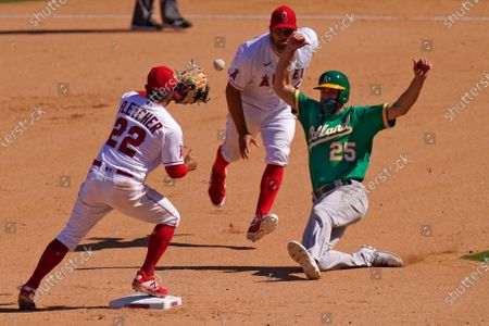 Los Angeles Angels first baseman Albert Pujols, center, tosses the ball to shortstop David Fletcher, left, to force out Oakland Athletics' Stephen Piscotty at second on a ball hit by Chad Pinder during the eighth inning of a baseball game, in Anaheim, Calif