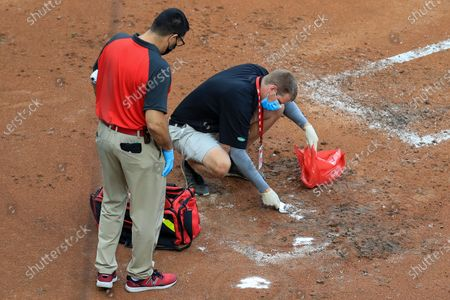 Members of the Reds' crew clean blood out of the dirt from MLB umpire Chris Conroy (98) in the first inning during a baseball game between the Kansas City Royals and the Cincinnati Reds in Cincinnati