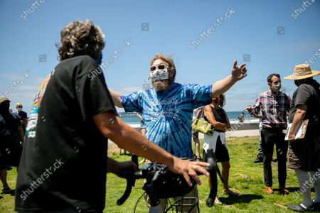Stock Image of Ocean Beach resident Matt Baker, who was unhappy about restrictions being put in place to encourage social distancing, argues with another resident as officials hosted a press conference at Ocean Beach Veteran's Plaza. The plaza has been the site of large gatherings in recent weeks, with drum circles and fire spinning taking place late into the night with little social distancing. The city fenced off the grass area at the plaza, but the fence was torn down on Tuesday and crews hauled it away.