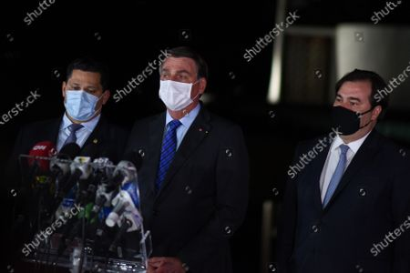 Brazilian President Jair Bolsonaro (C), attends a press conference with the president of the Lower House of Brazil, Rodrigo Maia (L) and the president of the Senate Davi Alcolumbre (R), at the Palacio de la Alvorada in Brasilia, Brazil, 12 August 2020. The president of Brazil, Jair Bolsonaro, assured that his government will respect the spending ceiling, which limits the annual increase in public budgets to the inflation of the previous year, and considered that the country's economy 'is reacting' despite the coronavirus pandemic.