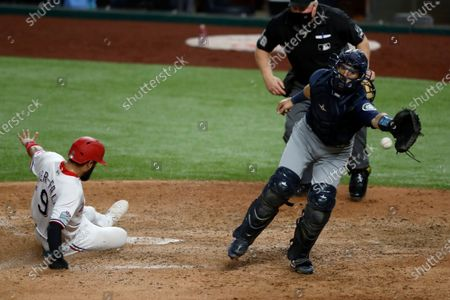 Texas Rangers' Isiah Kiner-Falefa scores on a Willie Calhoun single as Seattle Mariners catcher Austin Nola reaches for the throw during the eighth inning of a baseball game in Arlington, Texas, . Umpire Bill Miller watches