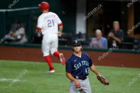 Seattle Mariners relief pitcher Taylor Williams stands by the plate after throwing a wild pitch that allowed Texas Rangers' Todd Frazier to score during the eighth inning of a baseball game in Arlington, Texas