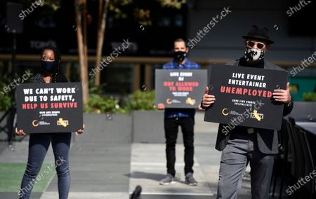 From left, live events professionals Ari Waller, Rob Corrall and Matthew McCallum hold signs at the ONE VOICE event, in honor of the live events industry which has been devastated by the COVID-19 pandemic, at L.A. Live in Los Angeles