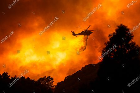 Helicopter drops water on the Lake Hughes fire in Angeles National Forest, north of Santa Clarita, Calif