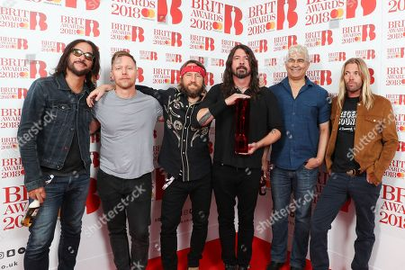 Rami Jaffee, Nate Mendel, Chris Shiflett, Dave Grohl, Pat Smear and Taylor Hawkins winners of the Best International Group award pose in the winners room during The BRIT Awards 2018