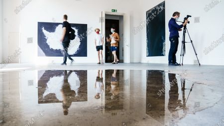 Visitors walk between the artworks  (L) 'Antarctic' (2010), and (R) 'Ocean VI' (2010) both by German photographer Andreas Gursky and (front) 'Berlin Puddle' (2020) by German artist Kirsten Pieroth, on display in the exhibition 'Down to Earth' at the Gropius Bau museum in Berlin, Germany, 13 August 2020. The exhibition reflects on the correlations between climate change agenda and our own 'operating system' behaviour. It is shown at the museum from 13 August to 13 September 2020.