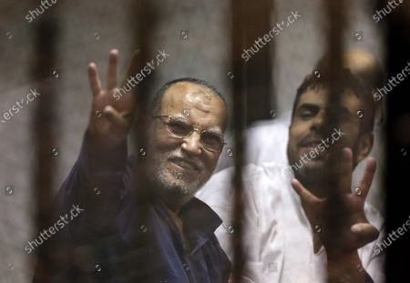 Senior Muslim brotherhood leader Essam el-Erian, left, flashes the four-fingered symbol of Rabaah that refers to the deadly dispersal of supporters of former Egyptian President Mohammed Morsi in August 2013, inside a makeshift courtroom at Egypt's National Police Academy, in Cairo, Egypt. Egyptian security officials said, that el-Erian, 66, has died of a heart attack in a Cairo prison where he was serving a 25-year sentence. The 66-year-old leader had been behind bars since 2013, following the military overthrow of Morsi, Egypt's first democratically-elected president, who had hailed from the Brotherhood's ranks