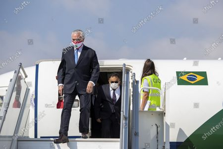 Former Brazilian President Michel Temer wears a mask with the colors of the Lebanese flag as he disembarks from a plane on his arrival to the Beirut International Airport, in Beirut, Lebanon, . Brazil's government sent a humanitarian mission to Lebanon on Wednesday in the wake of the Aug. 4 explosion in Beirut that killed more than 170 people, injured thousands and caused widespread destruction. Temer, whose parents were Lebanese, led a group of 13 people, including politicians, military personnel and businessmen to deliver aide