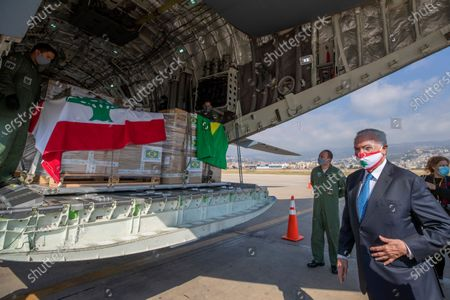 Former Brazilian President Michel Temer, wearing a mask with the colors of the Lebanese flag, checks boxes of aid supplies inside a cargo plane from the Brazilian army, on his arrival to the Beirut International Airport, in Beirut, Lebanon, . Brazil's government sent a humanitarian mission to Lebanon in the wake of the Aug. 4 explosion in Beirut that killed more than 170 people, injured thousands and caused widespread destruction. Temer, whose parents were Lebanese, led a group of 13 people, including politicians, military personnel and businessmen