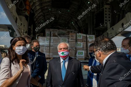 Brazilian former President Michel Temer, center, wearing a mask with the colors of the Lebanese flag, checks boxes of aid supplies inside a cargo plane from the Brazilian army, on his arrival to the Beirut International Airport, in Beirut, Lebanon, . Brazil's government sent a humanitarian mission to Lebanon in the wake of the Aug. 4 explosion in Beirut that killed more than 170 people, injured thousands and caused widespread destruction. Temer, whose parents were Lebanese, led a group of 13 people, including politicians, military personnel and businessmen