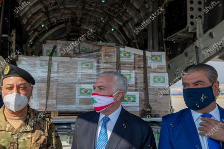 Former Brazilian President Michel Temer, center, wearing a mask with the colors of the Lebanese flag, checks boxes of aid supplies inside a cargo plane from the Brazilian army, on his arrival to the Beirut International Airport, in Beirut, Lebanon, . Brazil's government sent a humanitarian mission to Lebanon in the wake of the Aug. 4 explosion in Beirut that killed more than 170 people, injured thousands and caused widespread destruction. Temer, whose parents were Lebanese, led a group of 13 people, including politicians, military personnel and businessmen
