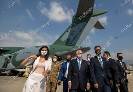 Former Brazilian President Michel Temer, whose parents were Lebanese, wears a mask with the colors of the Lebanese flag as he and a delegation including politicians, military personnel and businessmen arrive to the Beirut International Airport, in Beirut, Lebanon, . Brazil's government sent a humanitarian mission to Lebanon on Wednesday in the wake of the Aug. 4 explosion in Beirut that killed more than 170 people, injured thousands and caused widespread destruction