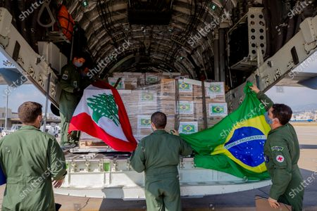 Brazilian air force personnel hold Brazilian and Lebanese flags on their arrival to the Beirut International Airport, in Beirut, Lebanon, . Brazil's government sent a humanitarian mission to Lebanon in the wake of the Aug. 4 explosion in Beirut that killed more than 170 people, injured thousands and caused widespread destruction