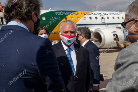 Former Brazilian President Michel Temer, center, wearing a face mask with the colors of the Lebanese flag to help curb the spread of the coronavirus, speaks with officials on his arrival to the Beirut International Airport, in Beirut, Lebanon, . Brazil's government sent a humanitarian mission to Lebanon in the wake of the Aug. 4 explosion in Beirut that killed more than 170 people, injured thousands and caused widespread destruction. Temer, whose parents were Lebanese, led a group of 13 people, including politicians, military personnel and businessmen