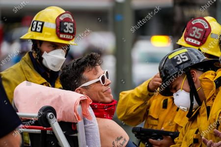 """Actor Steve-O is checked out by fire fighters after being brought down from being taped to a Hollywood billboard along Cahuenga Boulevard on Thursday, Aug. 13, 2020 in Los Angeles, CA. Steve-O, the star from MTV's Jackass series, is promoting his new project, """"Gnarly."""" (Kent Nishimura / Los Angeles Times)"""