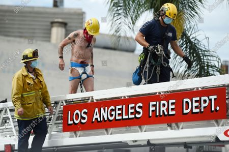 """Television personality Steve-O is led away by Los Angeles Fire Department personnel after he duct-taped himself to a billboard as a publicity stunt for his new multimedia special """"Gnarly,"""", in Los Angeles"""