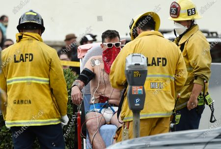"""Television personality Steve-O is evaluated by Los Angeles Fire Department personnel after he had duct-taped himself to a billboard as a publicity stunt for his new multimedia special """"Gnarly,"""", in Los Angeles"""