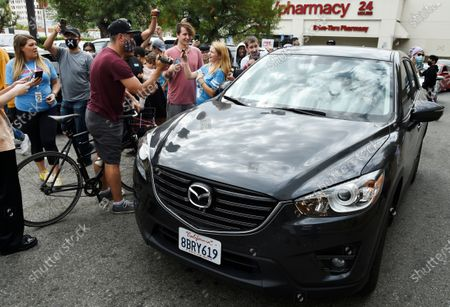 """Bystanders swarm a car carrying television personality Steve-O after he had duct-taped himself to a billboard as a publicity stunt for his new multimedia special """"Gnarly,"""", in Los Angeles. A Los Angeles Fire Department crew safely rescued the performer"""