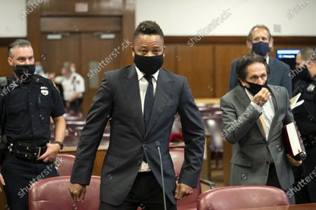 Actor Cuba Gooding Jr., center, approaches the defense table with his lawyer Marc Heller, foreground right, during a hearing in his sexual misconduct case, in New York. A judge ordered the courtroom outfitted with Plexiglas and other measures to prevent the spread of the coronavirus, which has delayed the trial indefinitely