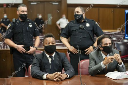 Actor Cuba Gooding Jr., center, sits at the defense table with his lawyer Marc Heller, during a hearing in his sexual misconduct case, in New York. A judge ordered the courtroom outfitted with Plexiglas and other measures to prevent the spread of the coronavirus, which has delayed the trial indefinitely