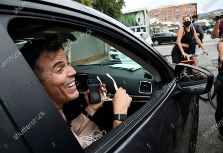"""Television personality Steve-O interacts with onlookers after he had duct-taped himself to a billboard as a publicity stunt for his new multimedia special """"Gnarly,"""", in Los Angeles. A Los Angeles Fire Department crew safely rescued the performer"""