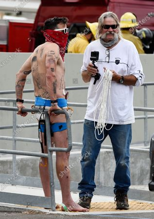 """Stock Image of Television personality Steve-O, left, waits to be driven away after he had duct-taped himself to a billboard as a publicity stunt for his new multimedia special """"Gnarly,"""", in Los Angeles. A Los Angeles Fire Department crew safely rescued the performer"""