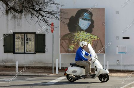 "Stock Image of Man rides his scooter in front of a marked version of Vladimir Tretchikoff's ""The Chinese Girl, The Green Lady"" painting in Stellenbosch, South Africa, . The public art is part of a series called Masked Masterpieces of masks superimposed on famous South African artworks to support Stellenbosch University students impacted by Covid-19"