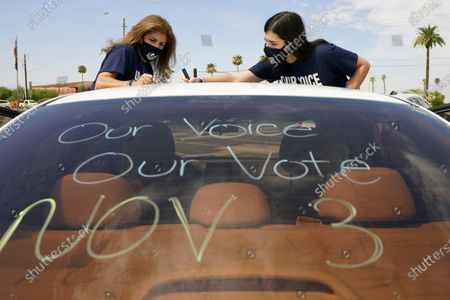 Patricia Santos, left, and her daughter Malia Santos mark their vehicle prior to a car rally, at the Capitol in Phoenix. A coalition of voting rights groups in Arizona have banded together with a lofty goal of getting one million people to vote this November