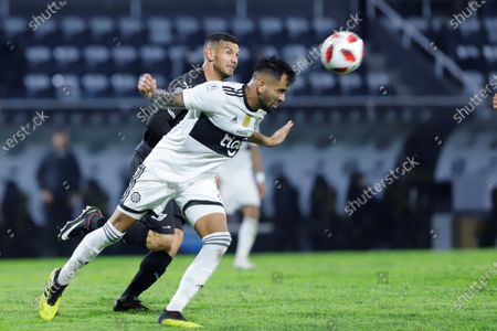 Carlos Rolon (R) of Olimpia in action against Adrian Martinez (L) of Libertad during the Paraguayan Primera Division Apertura Tournament soccer match between Club Olimpia and Club Libertad at Manuel Ferreira stadium in Asuncion, Paraguay, 13 August 2020.