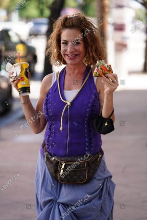 Claudia Wells eats pizza while on a walk