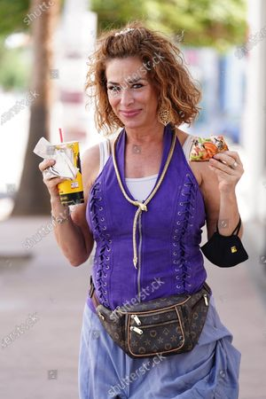 Stock Image of Claudia Wells eats pizza while on a walk